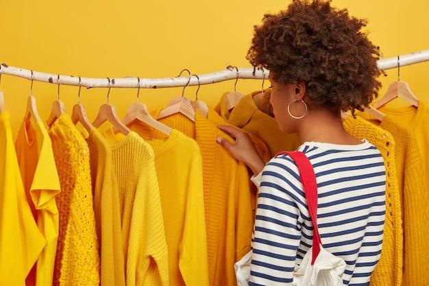 Vista traseira de mulher encaracolada em suéter de marinheiro, carrega bolsa, seleciona roupas em prateleiras, escolhe roupas para evento importante futuro, escolhe capa amarela em cabides, faz compras em loja de moda