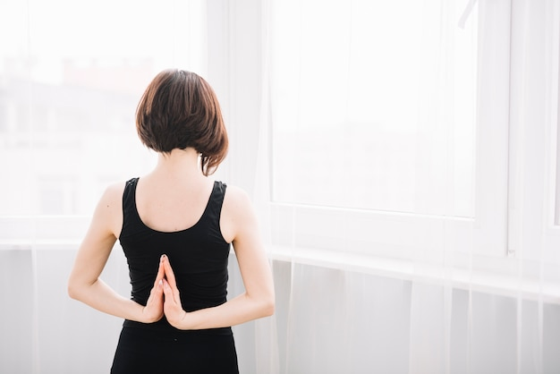 Vista traseira, de, mulher, esticar, dela, mão, durante, ioga