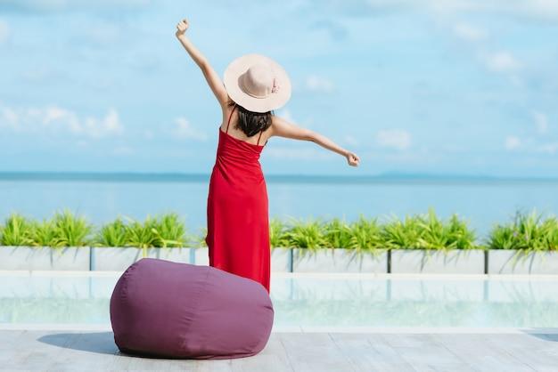 Vista traseira, de, mulher, esticar, e, relaxante, por, piscina