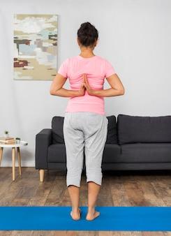 Vista traseira de mulher grávida fazendo exercícios em casa