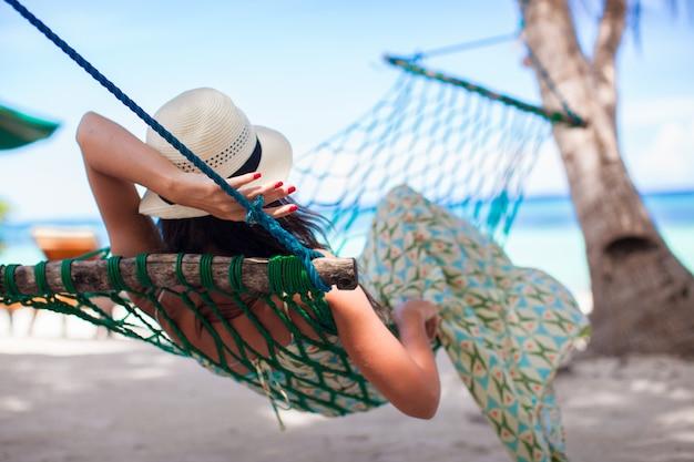 Vista traseira, de, mulher jovem, desfrutando, um, dia ensolarado, em, a, rede
