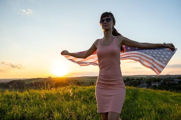 Vista traseira de mulher jovem feliz posando com a bandeira nacional dos eua ao ar livre ao pôr do sol. mulher positiva comemorando o dia da independência dos estados unidos. dia internacional do conceito de democracia.