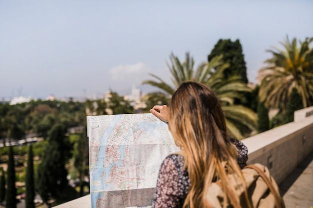 Vista traseira, de, mulher olha, em, mapa, para, direções