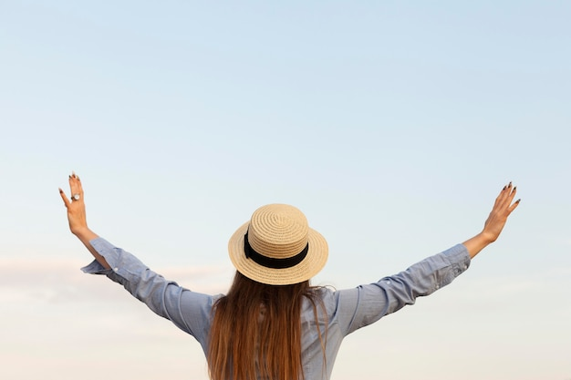 Vista traseira de mulher posando ao ar livre com os braços abertos