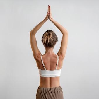 Vista traseira de mulher praticando ioga em casa