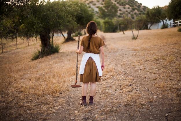 Vista traseira, de, mulher segura, ancinho, ficar, em, a, azeitona, pomar