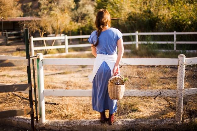 Vista traseira, de, mulher segura, cesta, ficar, perto, a, fazenda