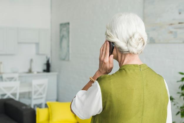 Vista traseira, de, mulher sênior, conversa num smartphone, casa