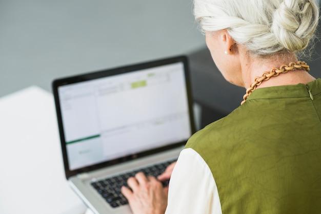 Vista traseira, de, mulher sênior, usando computador portátil