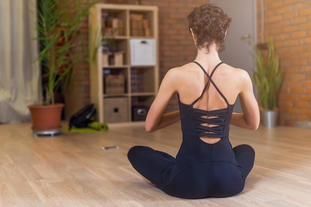 Vista traseira de mulher sentada em pose de lótus de ioga, relaxando e meditando na sala de estar