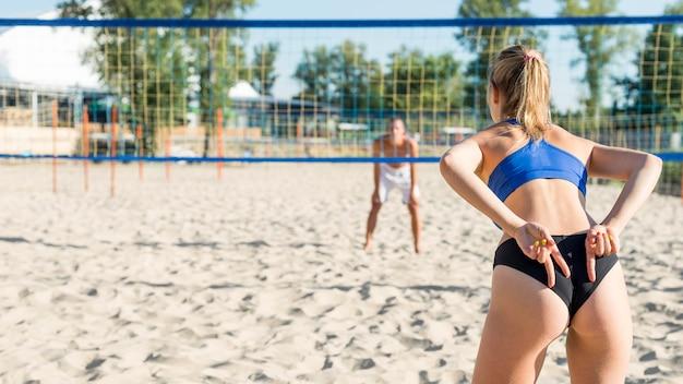 Vista traseira de mulher sinalizando colega de equipe com as mãos enquanto joga vôlei