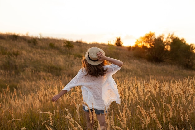 Vista traseira de mulher usando chapéu e posando no campo
