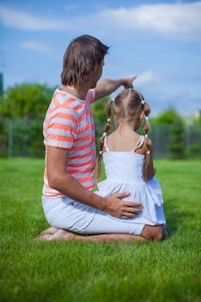 Vista traseira, de, pai, com, seu, filha, sentando, em, a, jarda, ao ar livre
