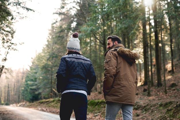 Vista traseira de pai e filho caminhando na floresta de outono