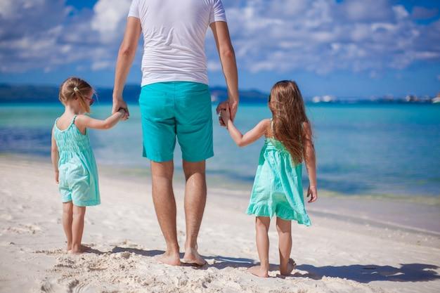 Vista traseira, de, pai jovem, e, seu, dois, pequeno, crianças, andar, por, a, mar