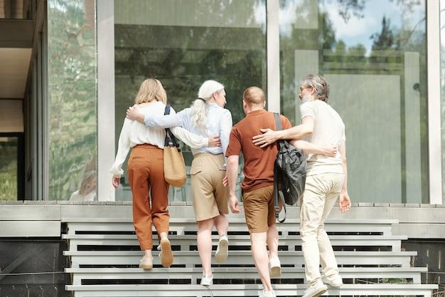 Vista traseira de pais idosos abraçando filho e filha adultos enquanto sobem as escadas para a casa de campo