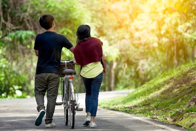 Vista traseira, de, par jovem, andar, junto, com, bicicleta, em, a, jardim