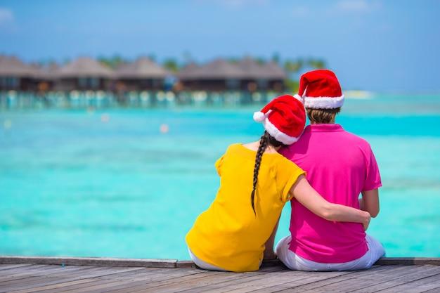 Vista traseira, de, par jovem, em, chapéus santa, ligado, madeira, jetty, em, natal, férias