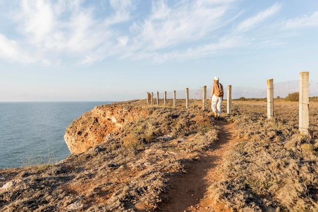 Vista traseira de pessoa caminhando em uma costa
