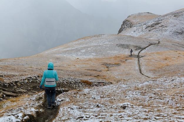 Vista traseira de pessoas com tapete turístico na trilha de caminhada em meio a nevoeiro e neve. foto com espaço de cópia