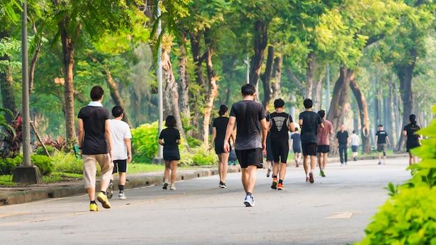 Vista traseira de pessoas correndo e caminhando em um parque com jardim para pedestres