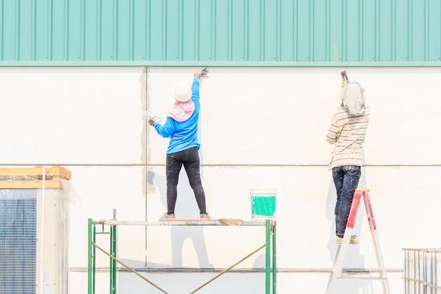 Vista traseira, de, pintura, trabalhador, reparar, parede, usando, um, pintura, espátula, mão, em, local construção