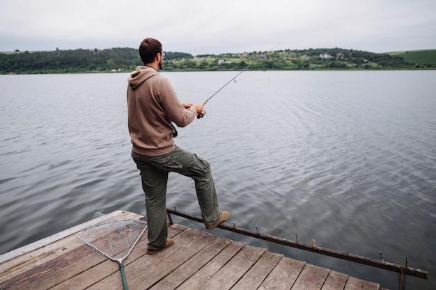 Vista traseira, de, posição homem, ligado, cais, pesca, em, a, lago