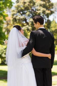 Vista traseira, de, recém casado, com, braços ao redor, parque
