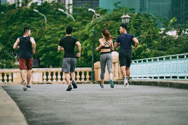 Vista traseira de três homens e uma garota correndo juntos em um dia de verão