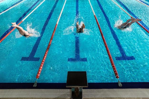 Vista traseira de três nadadores masculinos mergulhando em uma piscina