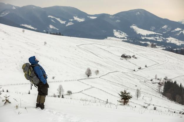 Vista traseira de turista caminhante em roupas quentes com uma mochila em pé na clareira da montanha