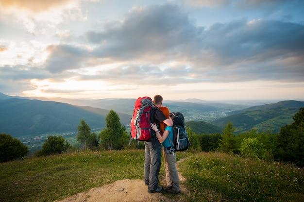 Vista traseira de turistas de casal com mochilas em pé abraçando