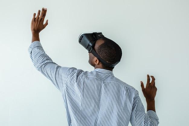 Vista traseira de um agradável homem afro-americano profissional usando óculos de realidade virtual enquanto escreve no quadro de realidade virtual