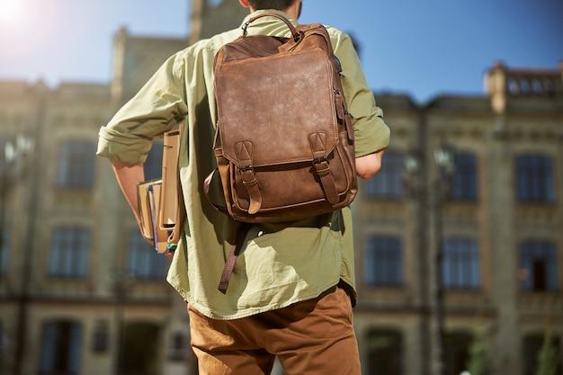 Vista traseira de um aluno com uma mochila de couro no ombro carregando seus livros didáticos