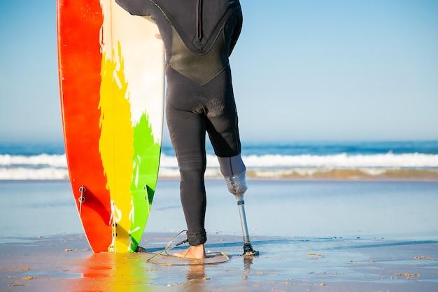 Vista traseira de um amputado irreconhecível em pé com uma prancha de surfe na praia