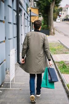 Vista traseira, de, um, andar homem, ligado, passeio, segurando, bolsas para compras