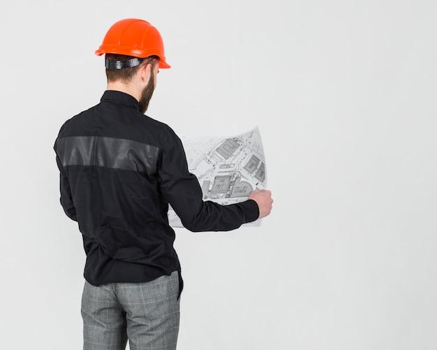Vista traseira, de, um, arquiteta macho, olhar, blueprint, sobre, a, fundo branco