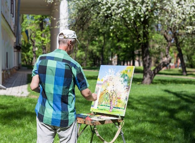Vista traseira de um artista masculino trabalhando ao ar livre no parque ou jardim
