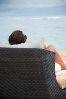 Vista traseira, de, um, assento mulher, ligado, um, cadeira chaise, ligado, praia, em, bali