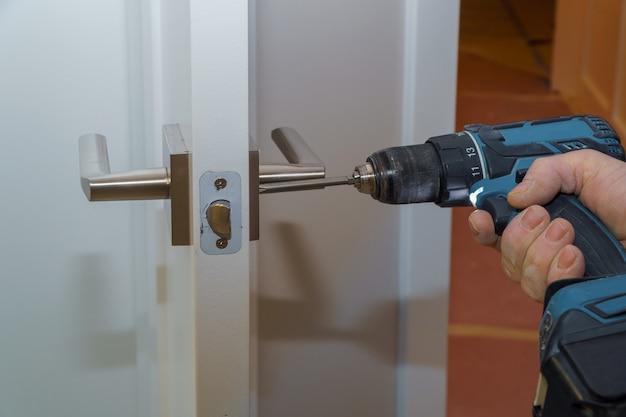 Vista traseira, de, um, bonito, homem procura, trabalhando, como, handyman, e, afixando, um, fechadura porta