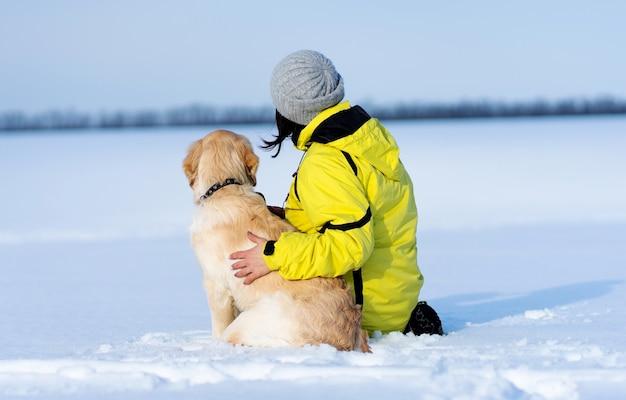 Vista traseira de um cachorro amigável e uma mulher sentada em um campo nevado