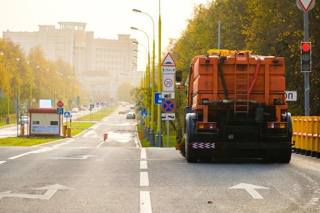 Vista traseira de um caminhão multifuncional laranja para limpeza de uma rua de asfalto.