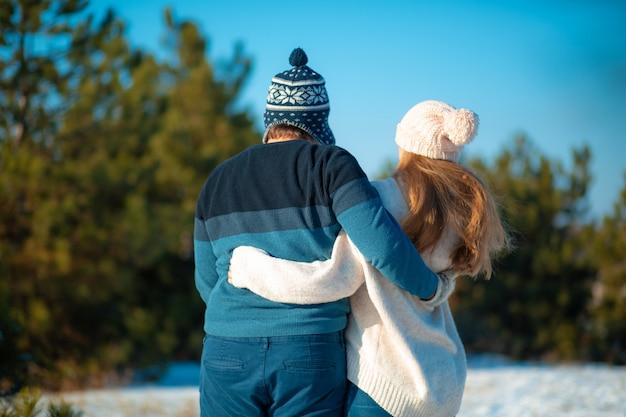 Vista traseira de um cara com uma garota em um abraço andar na floresta de inverno