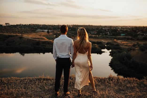 Vista traseira de um casal abraçando e apreciando o pôr do sol juntos.