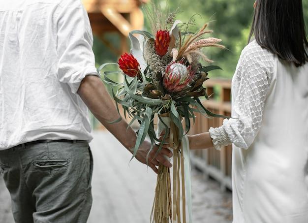Vista traseira de um casal apaixonado segurando um buquê com flores exóticas protea