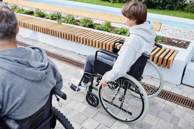 Vista traseira de um casal de amigos com deficiência andando em cadeira de rodas ao longo da rua ao ar livre
