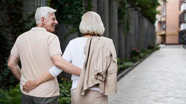 Vista traseira de um casal de idosos abraçado caminhando ao ar livre