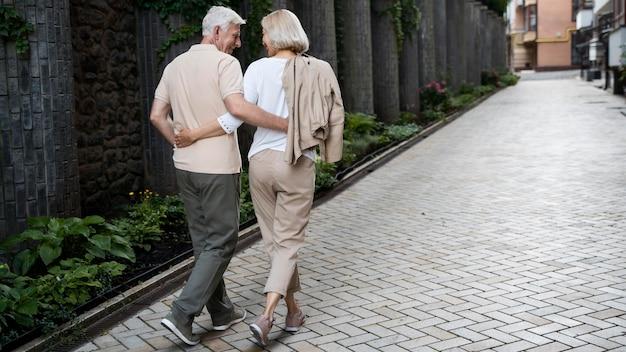 Vista traseira de um casal de idosos abraçado dando um passeio ao ar livre