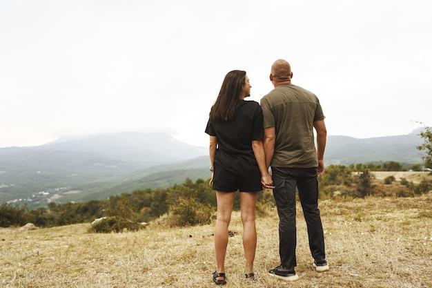 Vista traseira de um casal de pé olhando para as montanhas com neblina