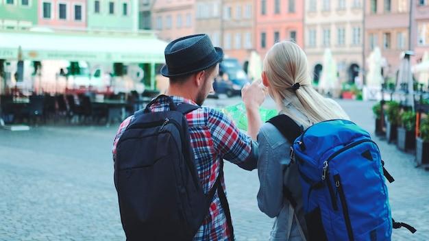Vista traseira de um casal de turistas com malas, verificando o mapa na praça central da cidade, eles discutindo seu novo ...